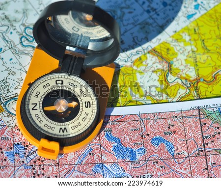 The compass on the map. Open the compass lies on topographic maps and casts a shadow over them. - stock photo