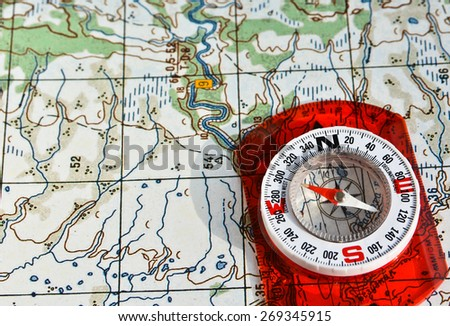 The compass on the map. Photo magnetic compass located on a topographic map. - stock photo