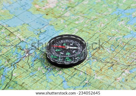 The compass on the map. The magnetic compass is located on a topographic map. - stock photo