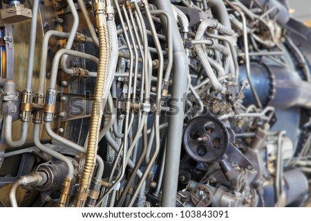 The complicated plumbing of tubing inside a jet engine - stock photo