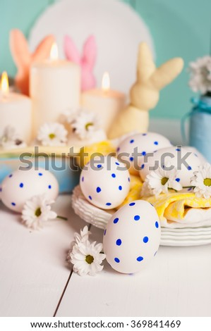 The composition consists of Easter eggs and colorful bunny on wooden background. - stock photo