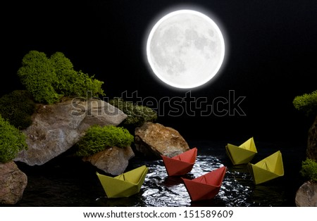 The composition of the stones, moss and paper boats, depicting sailing across the night sea between cliffs. The concept of a fragile dream world. - stock photo