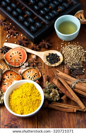 The composition with different spices and herbs on wooden table