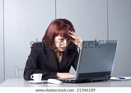 The concentrated beautiful business woman behind a desktop and the laptop - stock photo