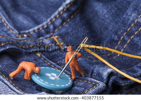 The concept for the fashion industry. Miniature workers sew on buttons big needle to jeans,close up. - stock photo