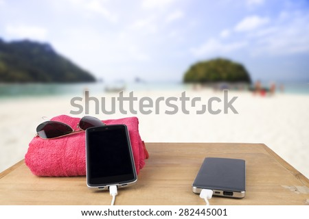 The concept idea. Red tower, sun glasses, mobile charging with power bank over wooden table on blur beach sand and blue sky background.  - stock photo