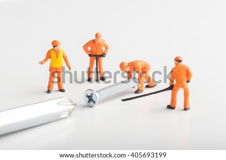 The concept of a collective solution to any problem. Miniature toy workers join a real screw with a screwdriver. Close-up view. - stock photo
