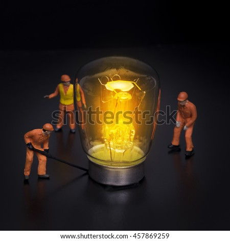 The concept of a collective solution to the problem. Miniature toy engineers solve technological problems. Close-up view. - stock photo