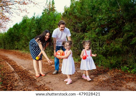 The concept of a happy family. Mom, Dad and two twins daughters are playing with a ball in the autumn, summer, alley in the park on nature.