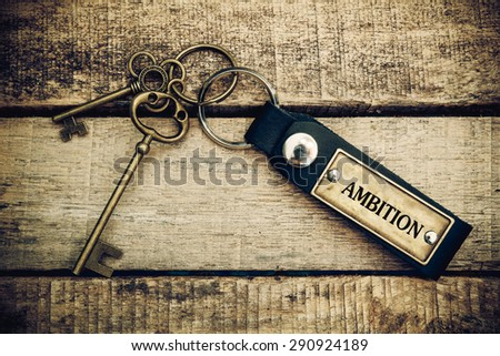 The concept of 'ambition' is translated by key and silver key chain. - stock photo