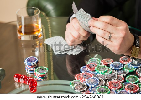 The concept of card games. Man playing poker at the poker table. Playing chip cards and whiskey on the table