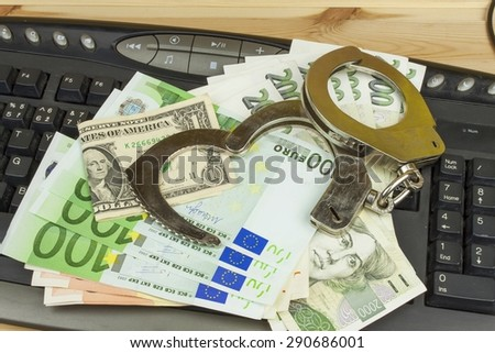 The concept of cybercrime. Criminal activity performed by computers and the Internet. Valid banknotes euro and the Czech koruna. Arrest cybercriminals, metal handcuffs and computer keyboard. - stock photo