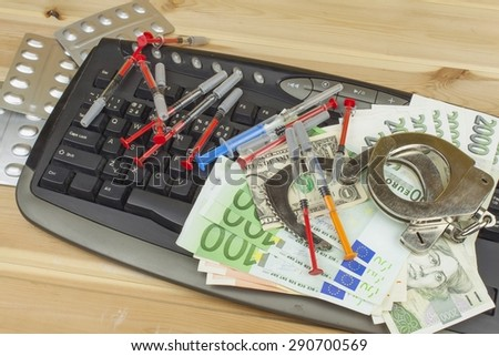The concept of cybercrime. Illegal sales of medications and drugs over the Internet. Valid banknotes euro and the Czech koruna. Arrest cybercriminals, metal handcuffs and computer keyboard. - stock photo