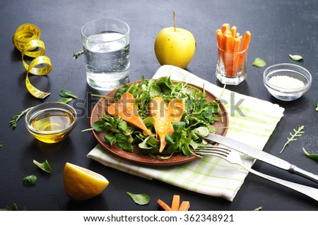 The concept of diet food. Salad with arugula and carrots in a clay plate. Beside the yellow sewing tape and the ingredients for salads, like as carrot, arugula, leaf mash, olive oil, half a lemon - stock photo