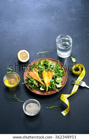 The concept of diet food. Salad with arugula and carrots in a clay plate. Beside the yellow sewing tape and the ingredients for salads. Place for writing text - stock photo