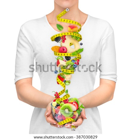 The concept of dieting. Girl in white t-shirt keeps your salad ingredients in air and measuring tape isolated on a white background. - stock photo