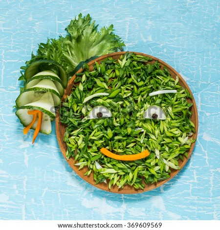 The concept of ecology, healthy food, preventing the spring avitaminosis - fresh green vegetables in the form of a smiling face. Symbol Earth Day. Square image - stock photo