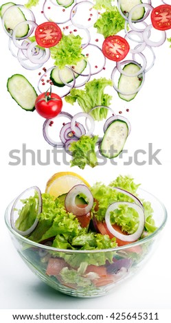 The concept of freshly prepared vegan salad. Fresh ingredients for a salad, such as tomatoes, purple onion, cucumber slices and lettuce, which fall in a bowl with salad. Vegetarian concept - stock photo