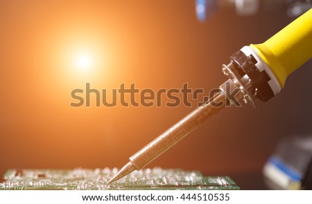 The concept of microelectronics. Soldering iron and circuit board - stock photo
