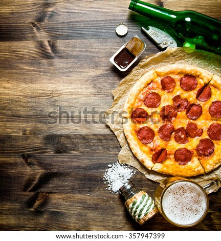 The concept of pizza with beer. Pepperoni pizza with beer on a wooden table. Top view - stock photo