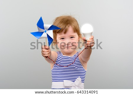The concept of renewable energy. Cute girl with led light bulb and windmill