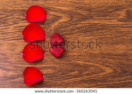 The concept of romance: the petals of red roses and two hearts on wooden background