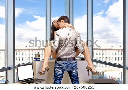 The concept of sexual relations on job. Young business couple are having sex in the workplace. - stock photo