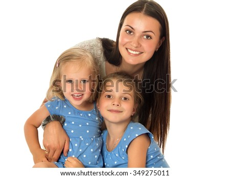 The concept of the celebration and the value of family relationships.Very beautiful young mother with long silky hair,tenderly embracing his beloved daughters. Little girls of different ages in