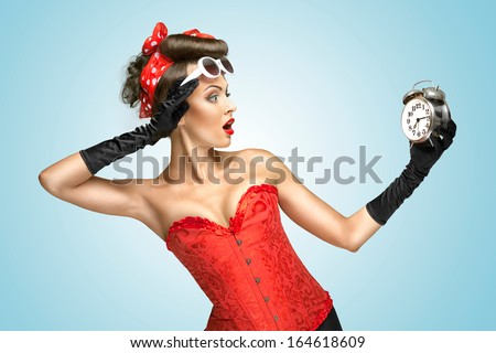 The conceptual photo of a girl in glamour underwear and gloves watching at the clock. - stock photo