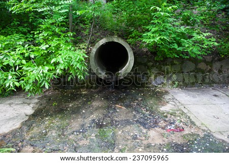 The concrete circular run-off pipe discharging water - stock photo
