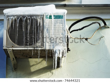 The conditioner covered with icicles on a yellow wall - stock photo