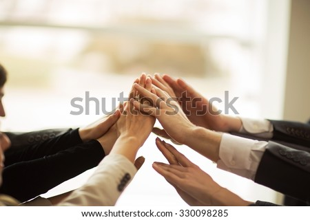 The conference of entrepreneurs. The folding of hands together and raise them up. - stock photo