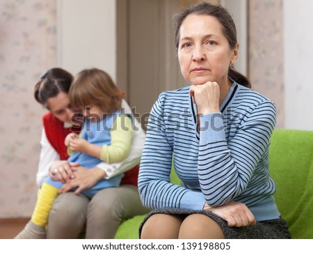 The conflict of intergenerational. Sad woman against daughter with baby at home - stock photo