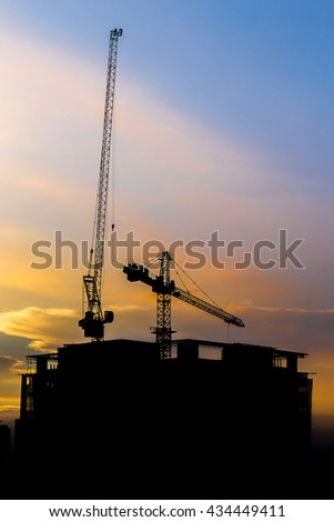 The construction crane and construction building with sunset time