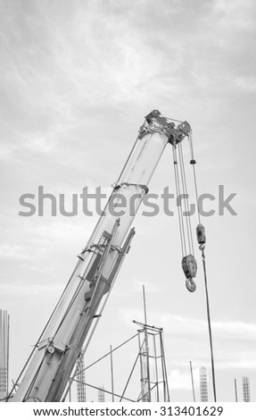 The construction crane for heavy lifting against a blue sky background. - stock photo