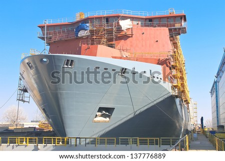 The construction of a new ship in dry dock shipyard - stock photo