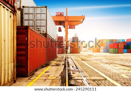 The container terminal at dusk, a large crane work. - stock photo