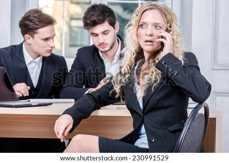 The conversation with the boss. Businesswoman talking on a cell phone while his colleague businessmen talking in the background sitting at table - stock photo