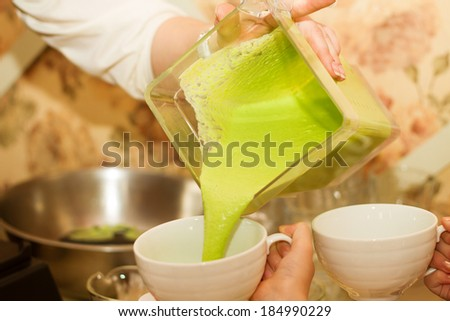 the cook pours pea cream soup in white ceramic cups