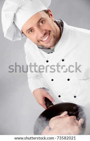 The cook prepares a hen in a frying pan - stock photo