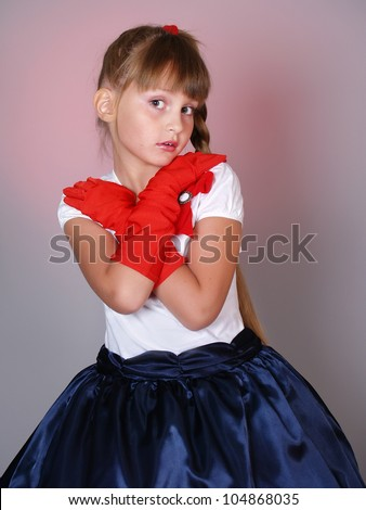 the coquettish little girl with beautiful big eyes in red gloves - stock photo