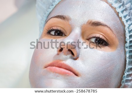 The cosmetic procedures for the face. Makeup artist applies invigorating mask on the face of the model. Beauty treatments in the spa salon. Facial Skin Care. - stock photo