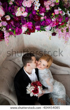the couple are facing each other and embracing on the vintage couch , the bride in a gray dress with lace, groom  in black trousers, white shirt. - stock photo