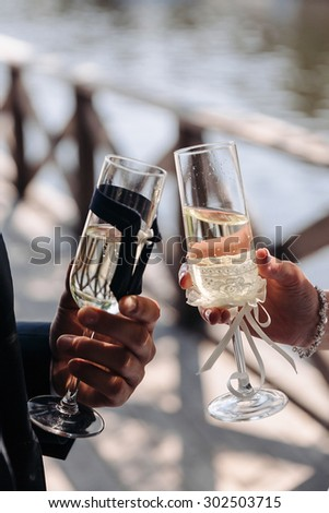 The couple, bride and groom holding a decorated, beautiful suites, a pair of wedding champagne glasses outdoors, close-up - stock photo