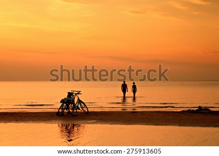 The couple is swimming toward the horizon in the quiet Baltic Sea at sunset on background of bicycles - stock photo
