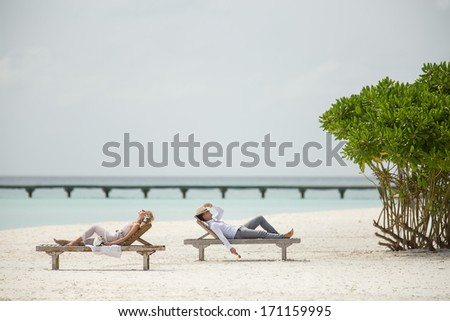 the couple lie on the sun loungers on the beach