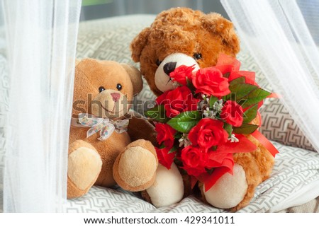 The couple of Teddy bear sitting on bed with bunch of red roses around by mosquito net./Teddy bear.  - stock photo