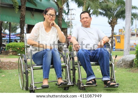the couple on wheelchair talking near the river with sunset by encourage  against the river background - stock photo