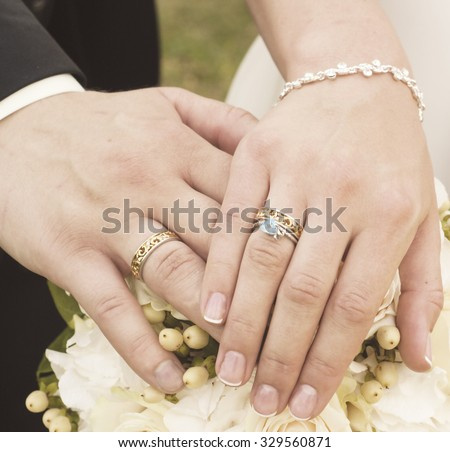The couple's with rings hands on the wedding bouquet - stock photo
