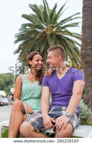 The couple sitting near the palm tree and spending great time - stock photo